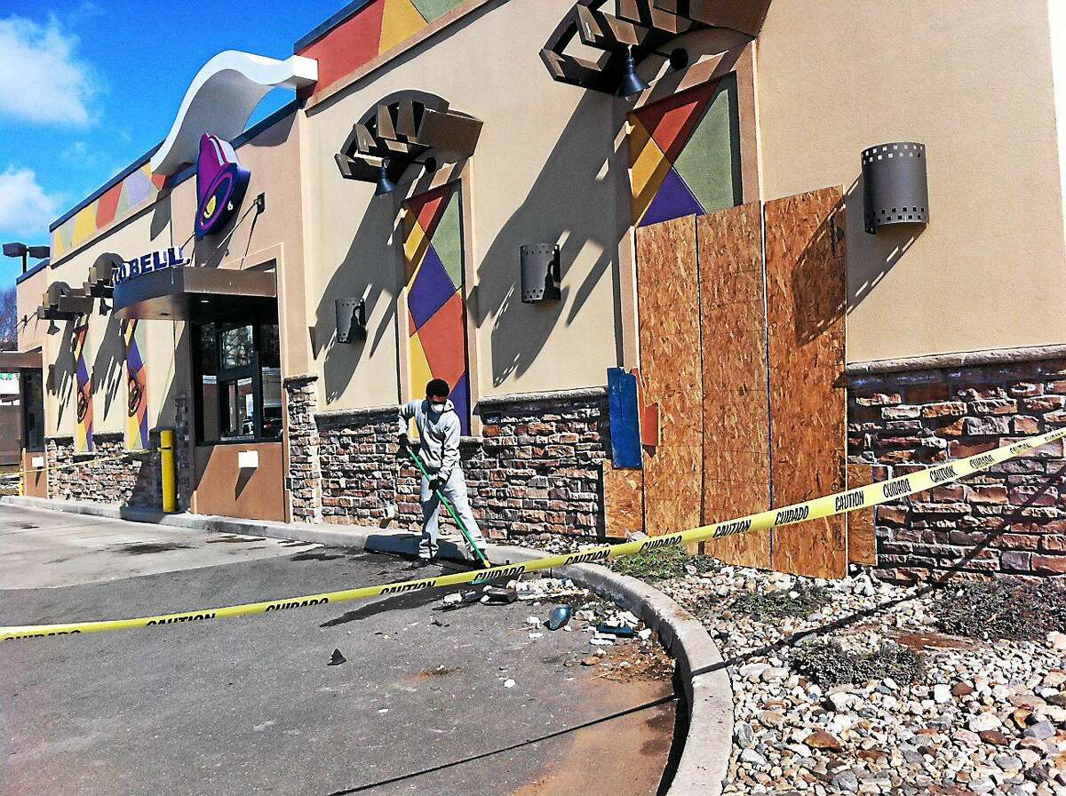 A worker cleans the area where a car crashed into Taco Bell at 2320 Dixwell Ave. in Hamden on Sunday, March 22, 2015.