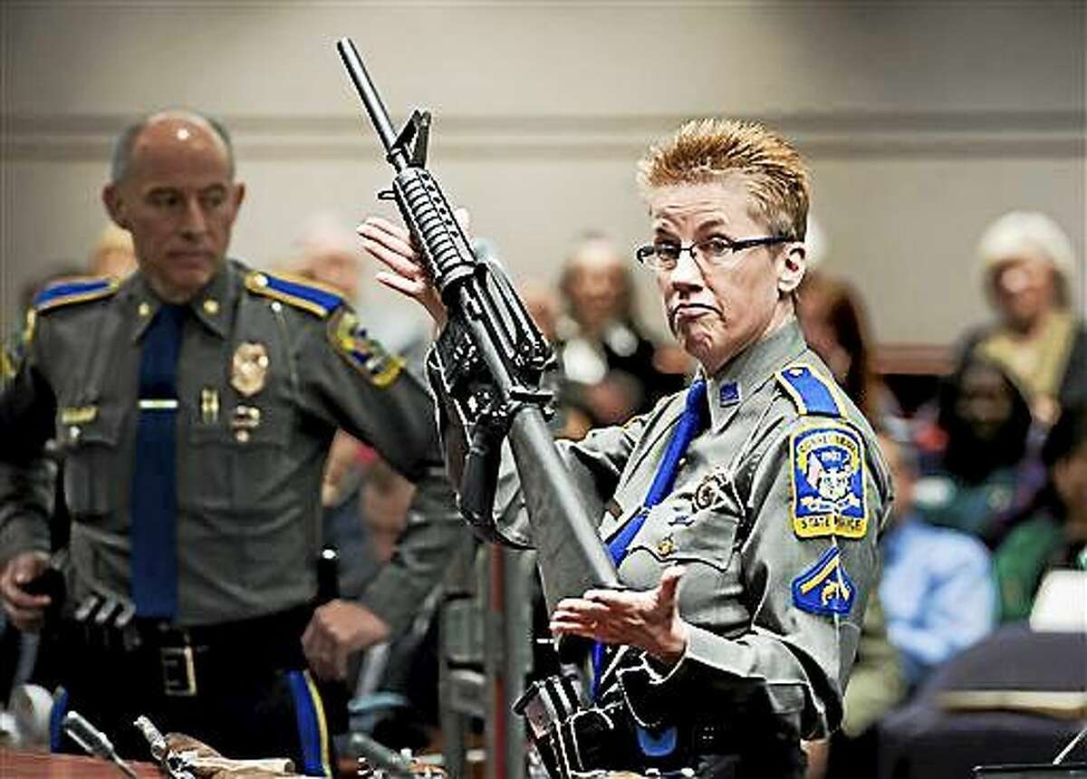 In this Jan. 28, 2013 photo, firearms training unit Detective Barbara J. Mattson, of the Connecticut State Police, holds up a Bushmaster AR-15 rifle, the same make and model of gun used by Adam Lanza in the Sandy Hook School shooting, for a demonstration during a hearing of a legislative subcommittee reviewing gun laws, at the Legislative Office Building in Hartford, Conn. The families of nine of the 26 people killed and a teacher injured on Dec. 14, 2012, at the Sandy Hook Elementary School filed a lawsuit against the manufacturer, distributor and seller of the Bushmaster AR-15 rifle used by Lanza in the shooting.