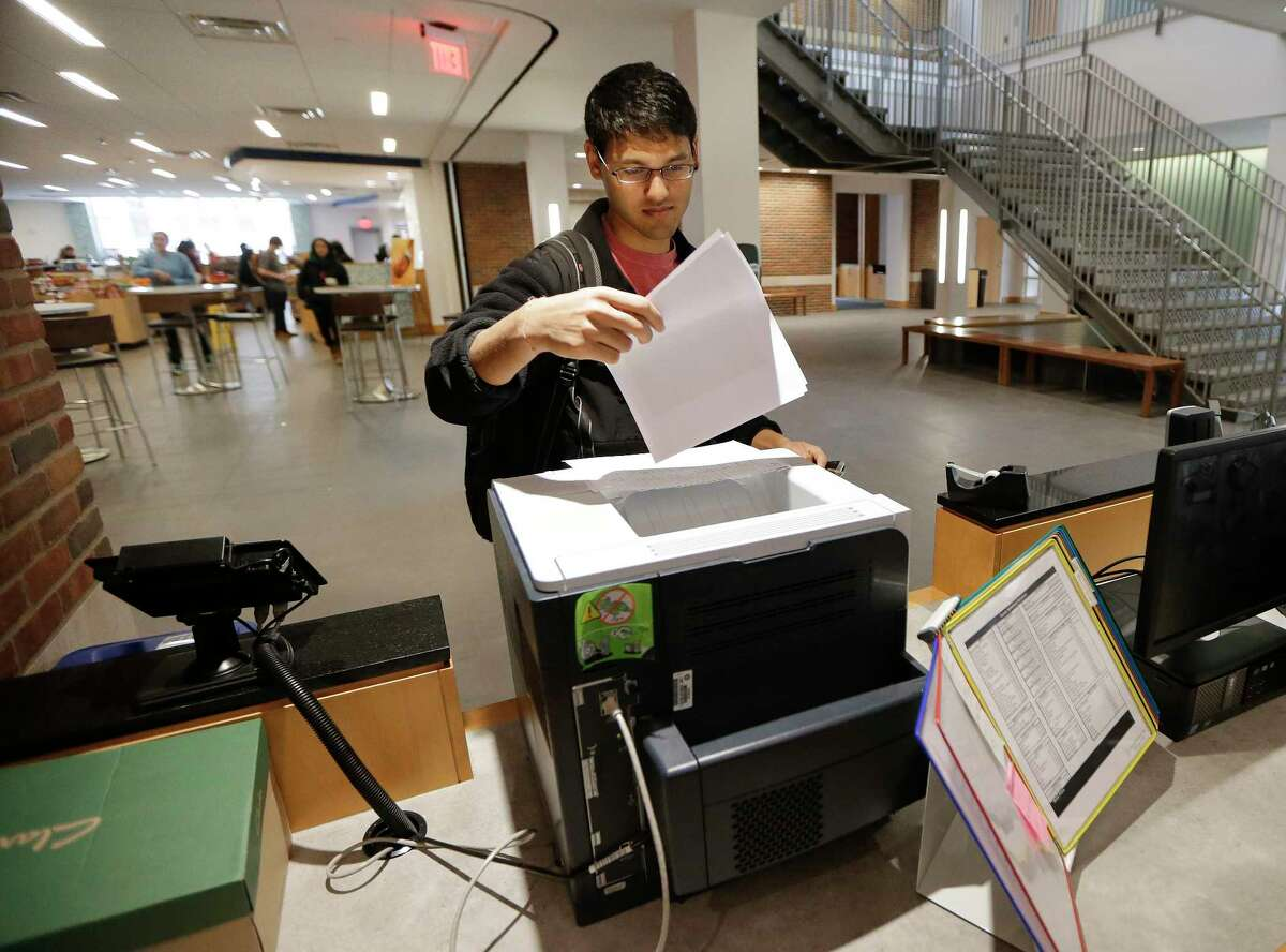 In this Feb. 24, 2015 photo, Vivek Shah, a sophomore resident advisor at Vanderbilt University's Moore College, uses the computer printer in the lobby of the student housing complex in Nashville, Tenn.