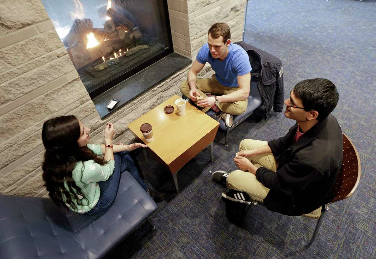 In this Feb. 24, 2015 photo, Vivek Shah, right, a sophomore resident advisor at Vanderbilt University, talks with friends Samara Lieberman, left, a senior from Detroit, and Tyler Shull, center, a sophomore from Chapel Hill, NC, by a fireplace in the great room in the Warren College and Moore College section of the Vanderbilt campus in Nashville, Tenn. Vanderbilt is one of a small but growing number of U.S. colleges and universities that have embraced a