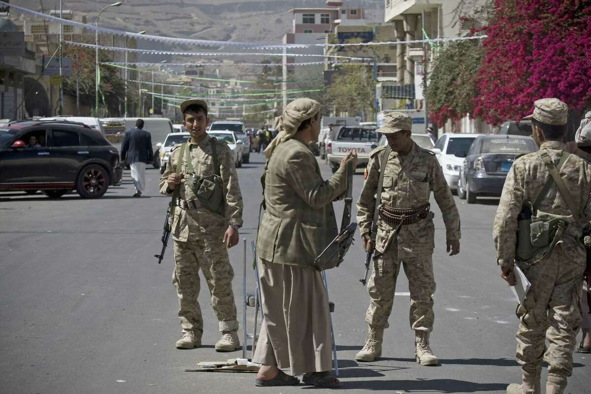 Houthi Shiite Yemeni wearing army uniforms stand guard on a street leading to the presidential palace in Sanaa, Yemen on Jan. 21, 2015. Authorities in southern Yemen have closed the country's second-largest airport there in protest over the Shiite rebels' power grab in the capital, Sanaa, which has plunged the nation deeper into chaos and threatens to fracture the country.