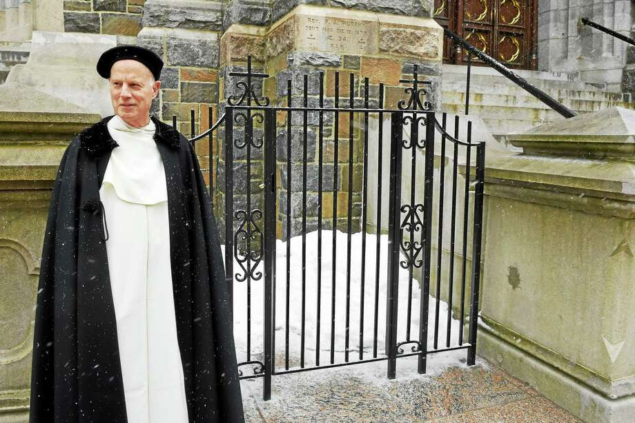 The Rev. Joseph Allen of St. Mary's Roman Catholic Church on Hillhouse Avenue in New Haven on Friday, standing in front of the church and the gated grave of the Rev. Patrick Murphy. Photo: Peter Hvizdak — New Haven Register   / ©2015 Peter Hvizdak