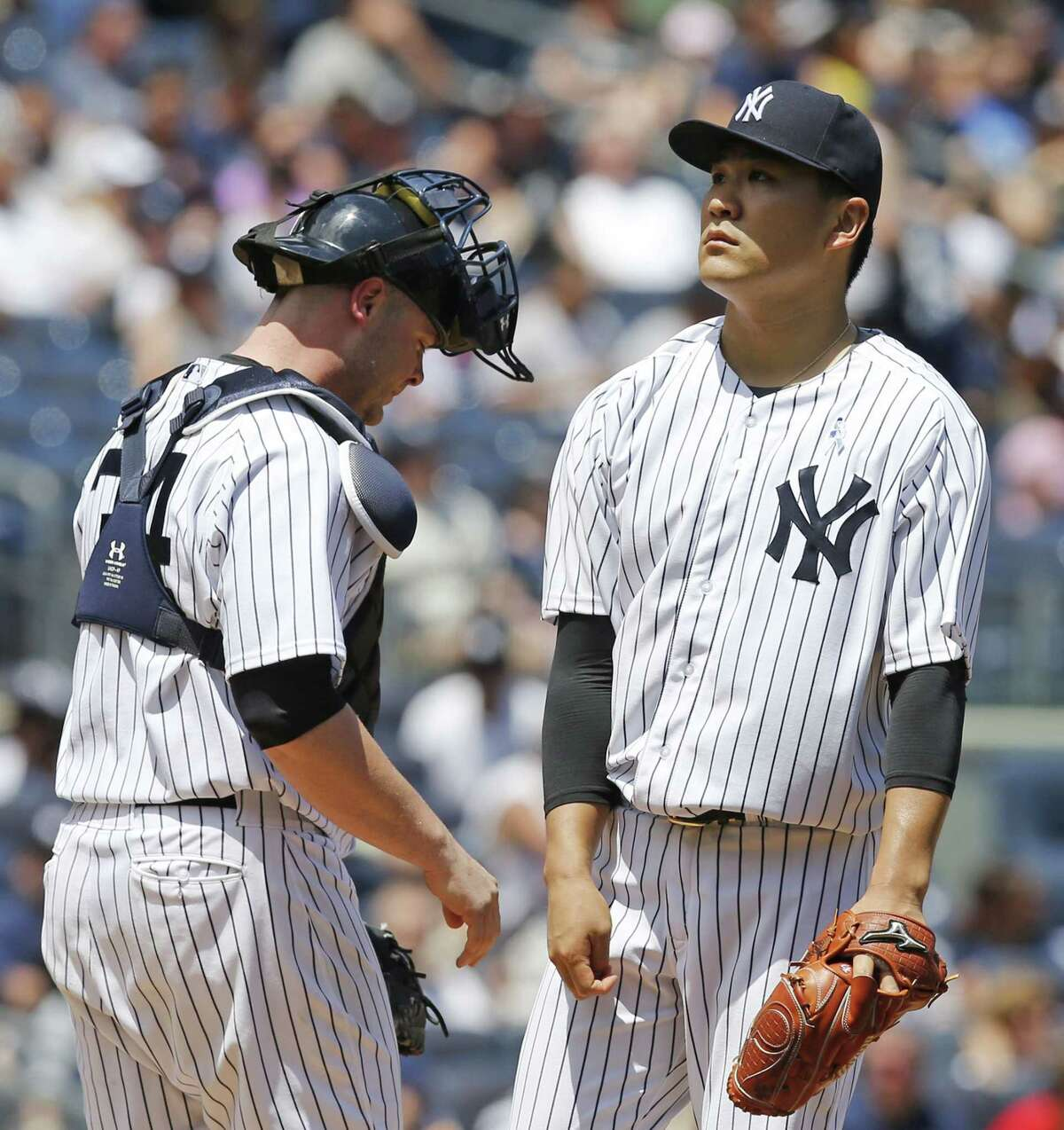 Yankees catcher Brian McCann, left, joints starting pitcher Masahiro Tanaka on the mound as Tanaka reacts after allowing a second-inning, two-run, single to Victor Martinez on Sunday.