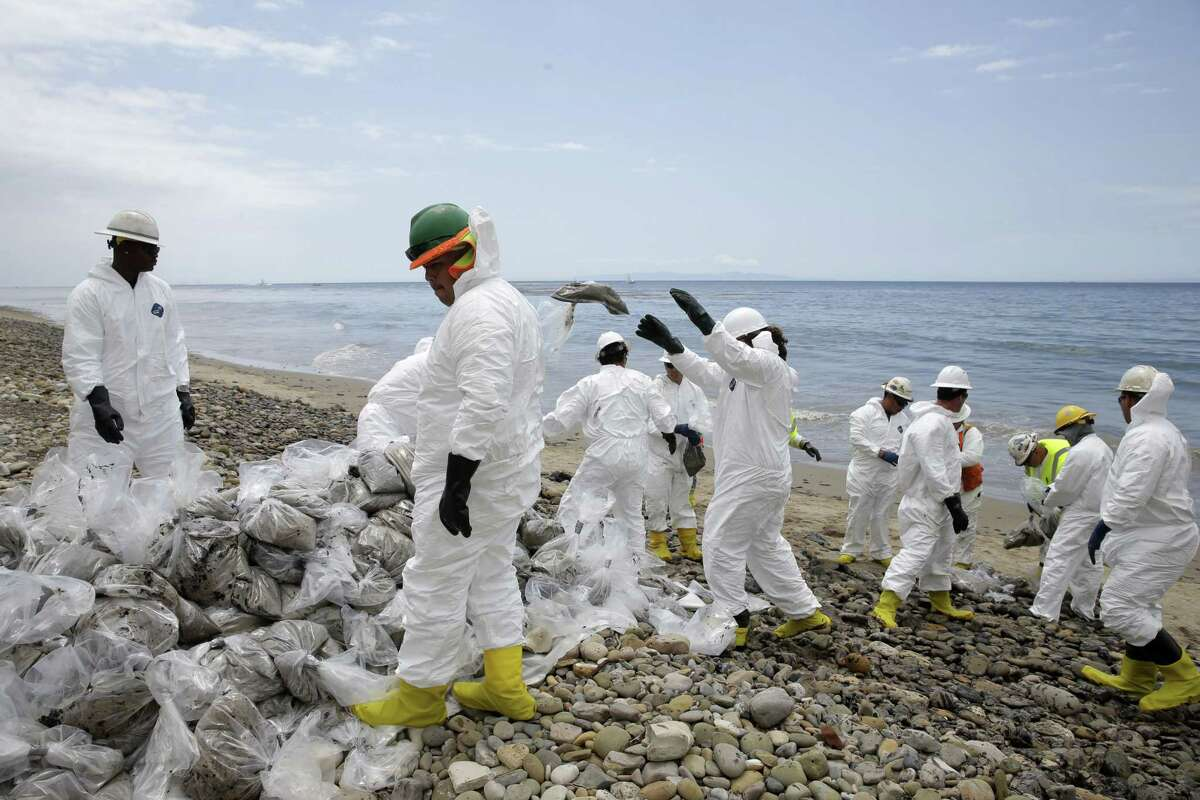 Clean up workers gather oil-contaminated sand bags at Refugio State Beach, north of Goleta, Calif., Thursday, May 21, 2015. More than 7,700 gallons of oil has been raked, skimmed and vacuumed from a spill that stretched across 9 miles of California coast, just a fraction of the oil escaped from a broken pipeline, officials said. (AP Photo/Jae C. Hong)