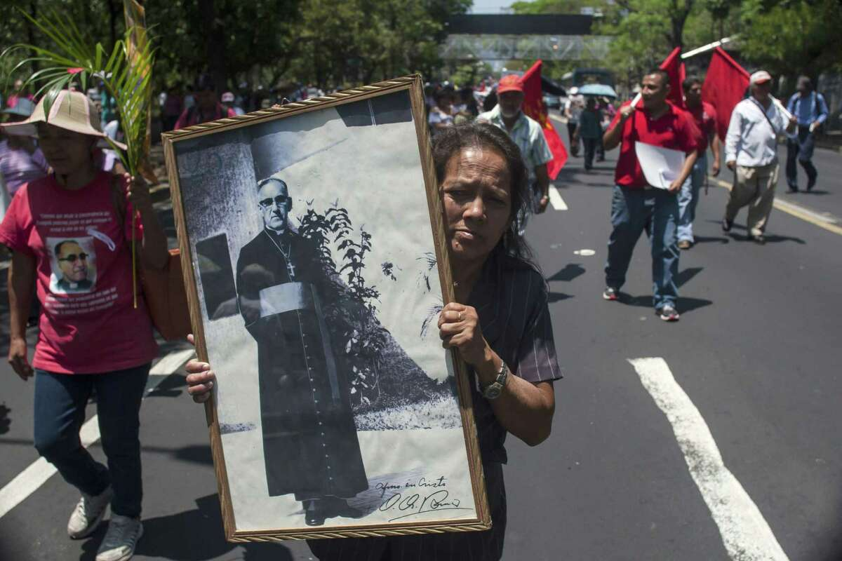 FILE - In this March, 24, 2015 file photo, Maria del Pilar Perdomo, 58, holds up a framed portrait of slain Archbishop of San Salvador, Oscar Arnulfo Romero, during a procession. The upcoming beatification of El Salvador Archbishop Oscar Romero is doing more than just giving Latin America its long-awaited saint-in-waiting. It has helped redefine the Catholic Church's concept of martyrdom and paved the way for others killed for doing God's work to follow in Romero's saint-making footsteps. (AP Photo/Salvador Melendez)