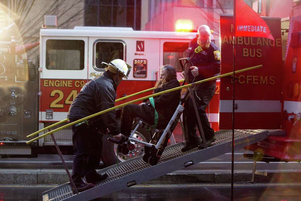 In this Jan. 12 file photo, a woman is transported in a wheelchair onto an ambulance as people are evacuated from a smoke filled Metro subway tunnel in Washington. Passengers were still asking when help would arrive 27 minutes after the smoke was first reported, District of Columbia officials said at the time.