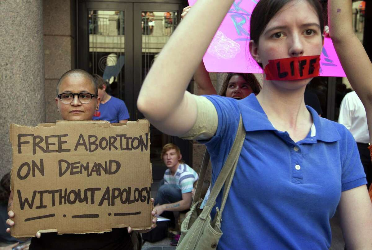 In a July 2, 2013 photo, pro-abortion rights supporter Yatzel Sabat, left, and anti-abortion protestor Amanda Reed demonstrate at the state Capitol in Austin, Texas. The Supreme Court is considering an emergency appeal from abortion providers in Texas, who want the justices to block two provisions of a state law that already has forced the closure of roughly half the licensed abortion clinics in the state.