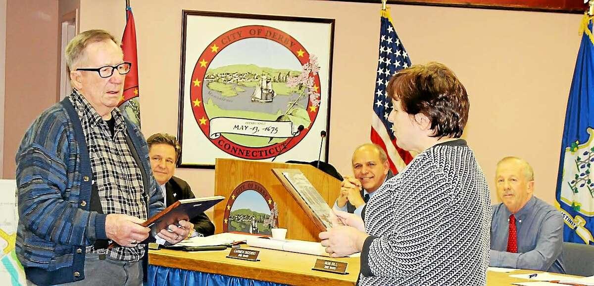 Derby Mayor Anita Dugatto presents Raymond G. Allen with a plaque naming him Derby's Citizen of the Year.
