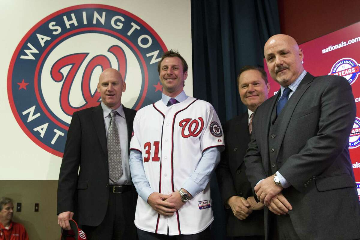 Washington Nationals pitcher Max Scherzer, second from left, poses for photographs during an introductory news conference Wednesday at Nationals Park in Washington.