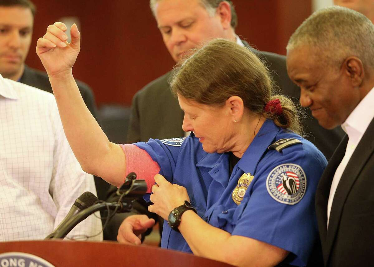 During a press conference the day after the incident, TSA agent Carol Richel shows the gunshot wound to the arm she suffered as she was chased by a machete-wielding man at the Concourse B security checkpoint of Louis Armstrong International Airport. AP Photo/NOLA.com The Times-Picayune