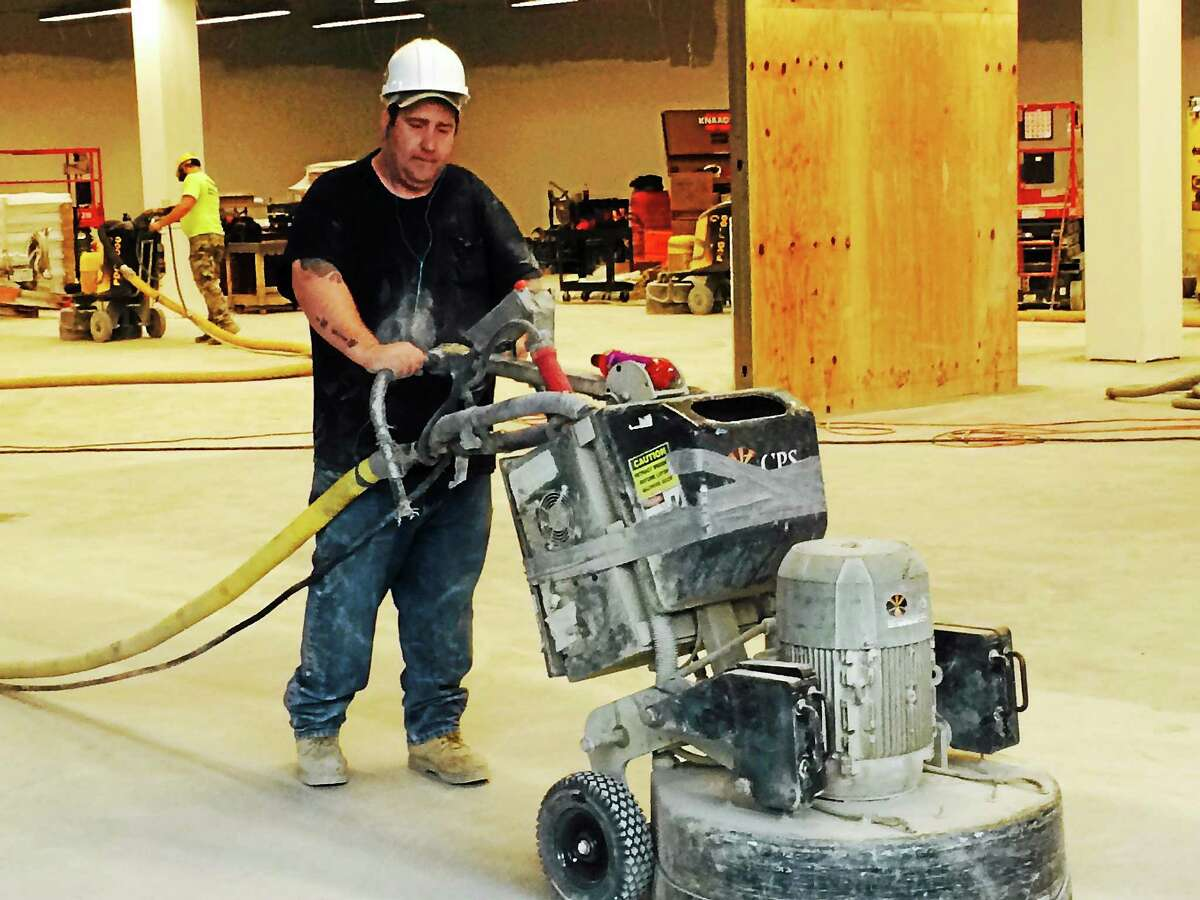 A construction worker pushes a large sander across an unfinished floor at Tanger Outlet Center at Foxwoods Tuesday.
