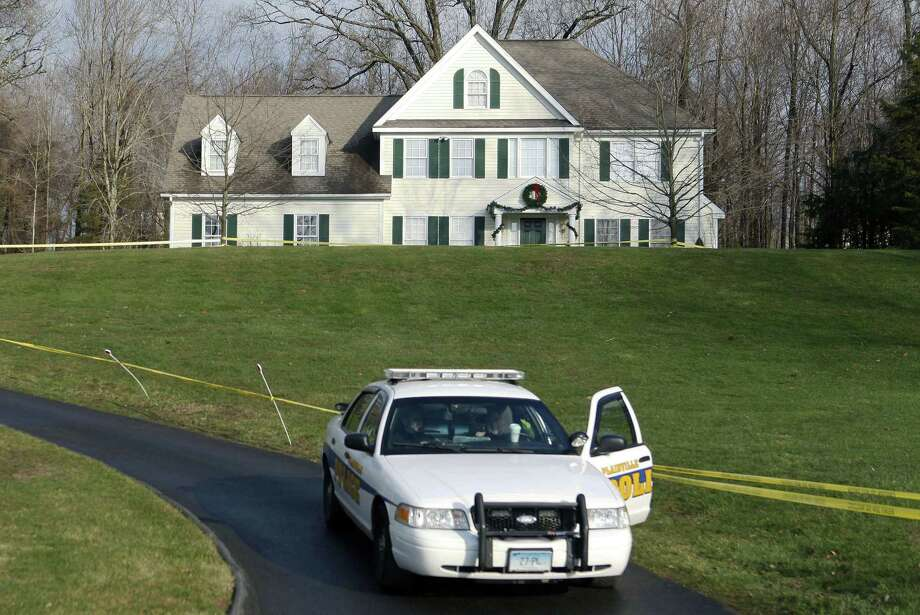 FILE - In this Dec. 18, 2012 file photo a police cruiser sits in the driveway of the home of Nancy Lanza, in Newtown, Conn. The Colonial-style home where Newtown school shooter Adam Lanza lived with his mother has been transferred to the town in a deal with a bank. Nancy Lanza was killed there by her son before he forced his way into Sandy Hook Elementary School, Dec. 14, 2012, in Newtown, where he killed 20 first-graders and six educators. The future use of the house and property will be decided later. (AP Photo/Jason DeCrow, File) Photo: AP / FR103966 AP