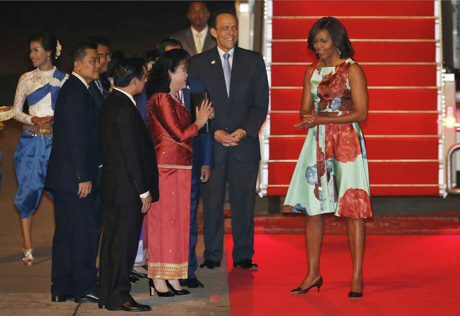 U.S. first lady Michelle Obama is greeted by Bun Rany, the first lady of Cambodia, while U.S. Ambassador William Todd, center, looks on, at Siem Reap International Airport on Friday, March 20, in Siem Reap, Cambodia. Mrs. Obama's Friday evening arrival in Cambodia comes after a three-day visit to Japan. (AP Photo/Wong Maye-E) Photo: AP / AP