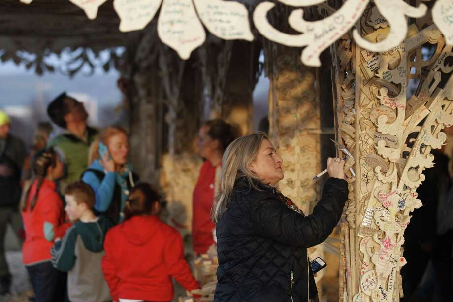 In this Photo taken Wednesday March 18, 2015, a woman writes a message on the intricately hand crafted wooden tower, on a hill overlooking Londonderry, Northern Ireland.  Attracting thousands of people to write messages, the 72 foot tall (22 meter) wooden tower designed by American sculptor David Best, is scheduled to be burned to the ground Saturday night. In a region normally marked by divisions, and where bonfires are normally burned as acts of sectarian division, this ornate wooden tower is attracting both Protestant and Catholic admiration, in an atmosphere of harmony. (AP Photo/Peter Morrison) Photo: AP / AP