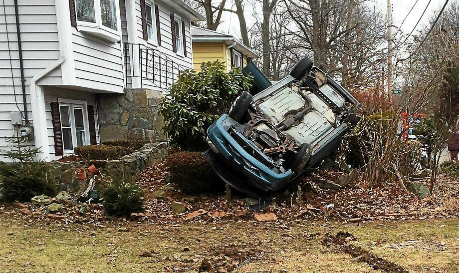 A car crashed in a yard on West Spring Street in West Haven Friday morning. Photo: Wes Duplantier — New Haven Register