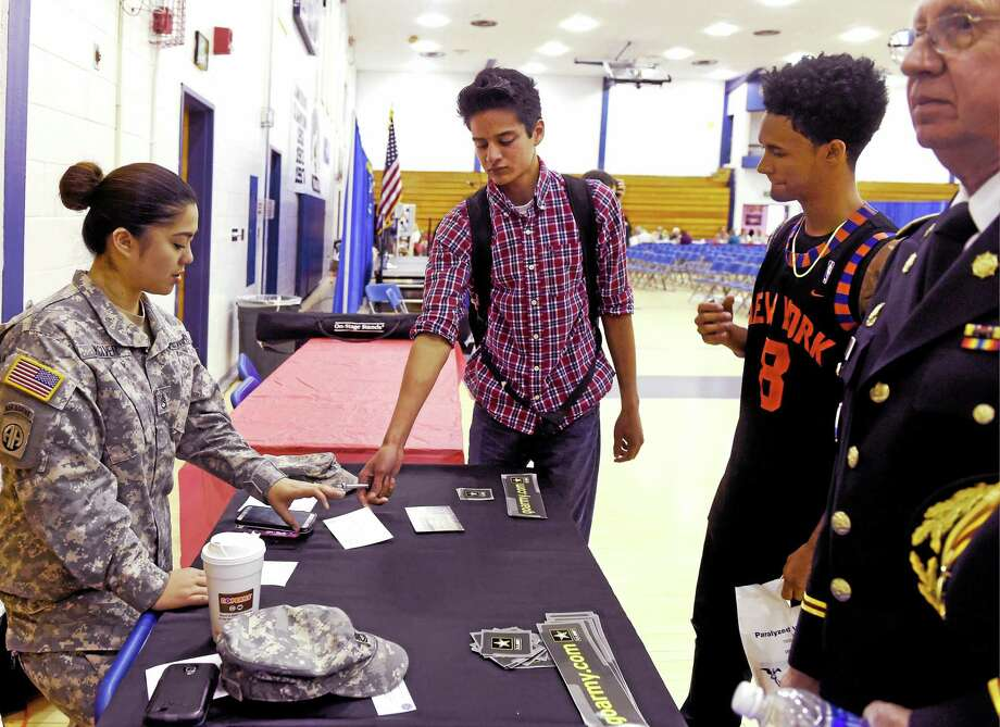 Lucas Carmonda, 17, a Hamden High School junior, third from left, gives a signed Lead Card to Army Staff Sgt. Anncatherine McIver , an Army recruiter at the New Haven Recruiting Center, as classmate Joseph Andino, 17, watches during Hamden Veterans Awareness Day at Quinnipiac University Thursday. The Lead Card gives the recruiter information on how to contact a parent whose underage child is interested in enlisting in the Army or the Army Reserve. Photo: Peter Hvizdak — New Haven Register   / ©2015 Peter Hvizdak