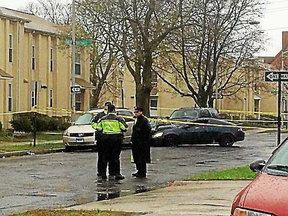 Police on the scene of a fatal shooting Monday afternoon. A blue coupe crashed into parked car, seen in the background.