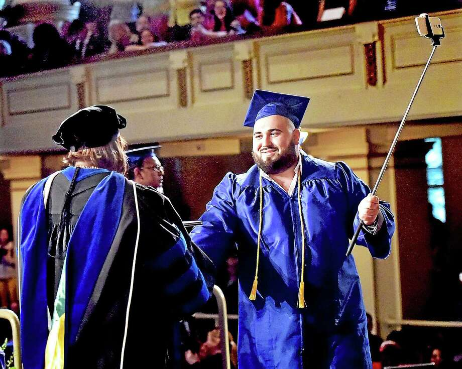 John Biba, a member of the class of 2015 at Gateway Community College, captures his graduation with his smartphone on a selfie stick while receiving an associate degree in business administration with an accounting option Thursday at Woolsey Hall at Yale University in New Haven. Photo: Catherine Avalone — New Haven Register   / New Haven RegisterThe Middletown Press