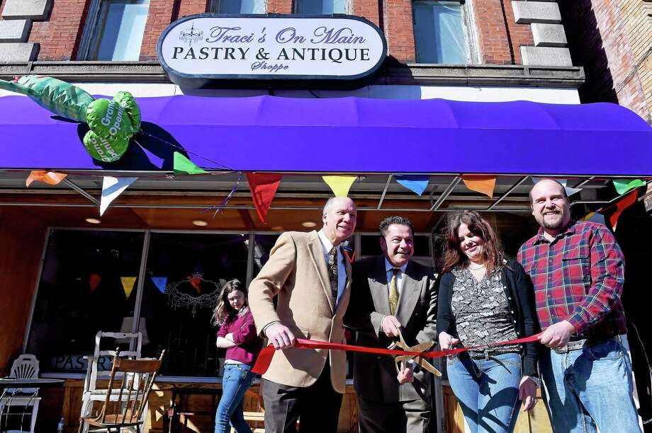 From left, Bill Purcell, president of the Greater Valley Chamber of Commerce, Ansonia Mayor David Cassetti, and Traci and Scott Grim, owners of Traci's on Main Pastry & Antique Shoppe, cut the ribbon in front of the store at 94 Main St. in Ansonia Thursday. Photo: Arnold Gold — New Haven Register