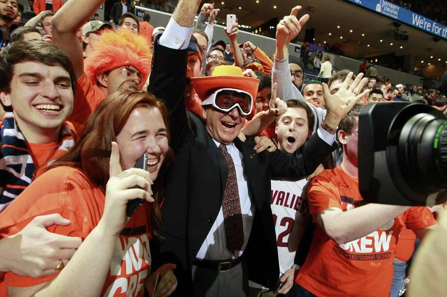 Sportcaster Dick Vitale, center, poses with Virginia fans before a game against Louisville on Feb. 7 in Charlottesville, Va. Photo: Andrew Shurtleff — The Associated Press   / FR82550 AP
