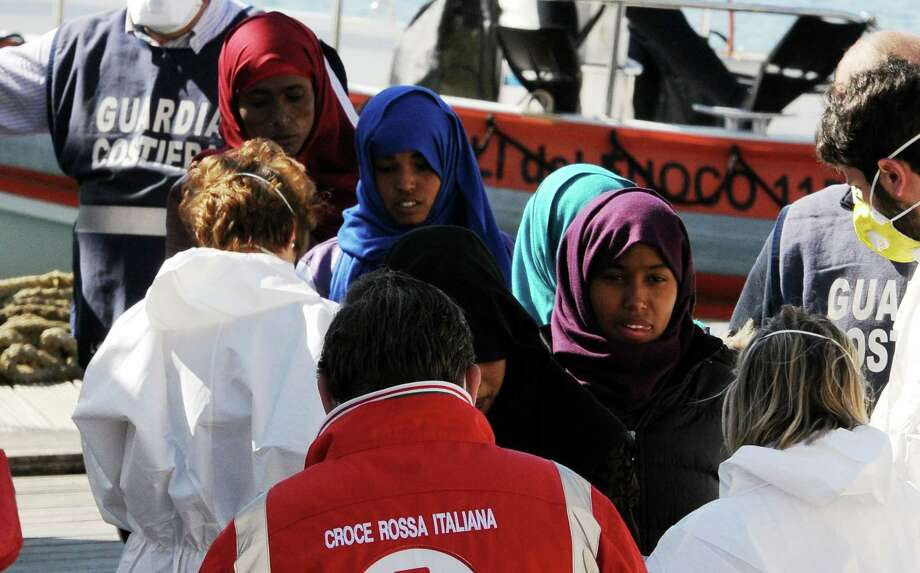 Migrants receive first aid upon disembarking at Palermo's harbor, Italy, after being rescued at sea on April 18, 2015. Italian ships have picked up some 10,000 people, many of them refugees of war and persecution, over the past week, an unprecedented number in such a short period. Photo: AP Photo/Alessandro Fucarini   / AP