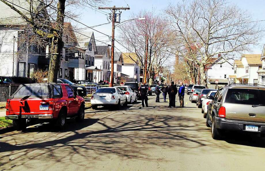 (Kate Ramunni/New Haven Register)  New Haven police investigate a double shooting that left one 16-year-old dead. The incident occurred on Exchange Street early Sunday, April 19, 2015. Photo: Journal Register Co.