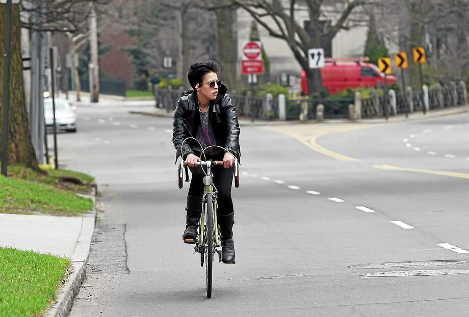 Bicyclist on Whitney Ave. in New Haven near the Yale School of Management  Friday afternoon, April 17, 2015. Photo: (Peter Hvizdak - New Haven Register)   / ©2015 Peter Hvizdak