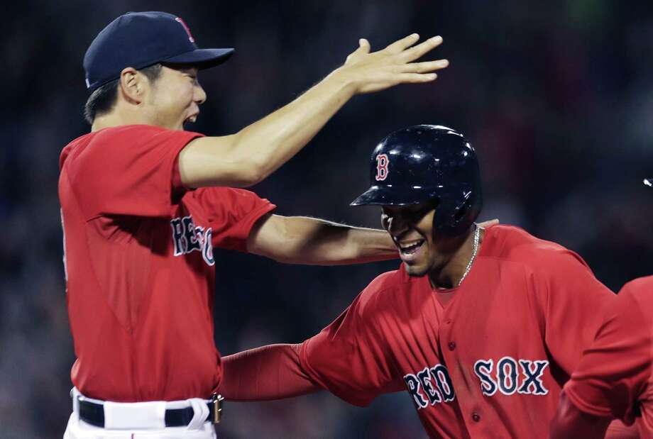 Boston Red Sox's Xander Bogaerts, right, is congratulated by relief pitcher Koji Uehara after driving in teammate Mike Napoli for the game-winning run to break a 2-2 tie, during the ninth inning of a baseball game against the Baltimore Orioles at Fenway Park in Boston, Friday, April 17, 2015. Uehara got the win in the 3-2 victory. (AP Photo/Charles Krupa) Photo: AP / AP