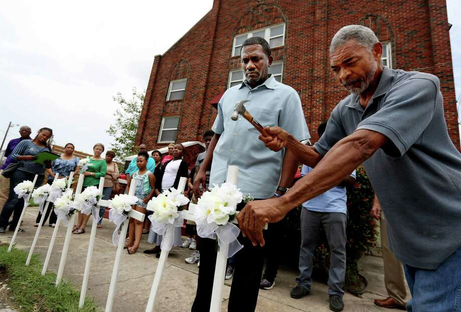 The Rev. Reginald Honors gets assistance from David Hogan to place one of nine crosses in memory of the victims killed in the shooting in Charleston, S.C., Friday, in front of Brown Chapel African Methodist Church in Houston. The crosses were placed in front of Brown Chapel after a Healing Gathering for members of the community who discussed any crisis of faith, fears or concerns. Photo: Houston Chronicle Via AP   / Houston Chronicle