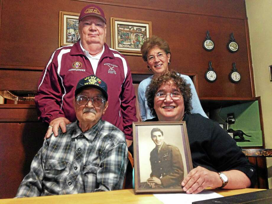Front row: WWII veteran Dr. Anthony Buemi with daughter and North Haven Third Selectman Sally Buemi. Back row: Dan Riccio Jr., commander of Post 76, and Buemi's daughter Mary LoPresti. The photograph is of Dr. Buemi in 1945 after being discharged from the Army. Photo: Kate Ramunni — New Haven Register