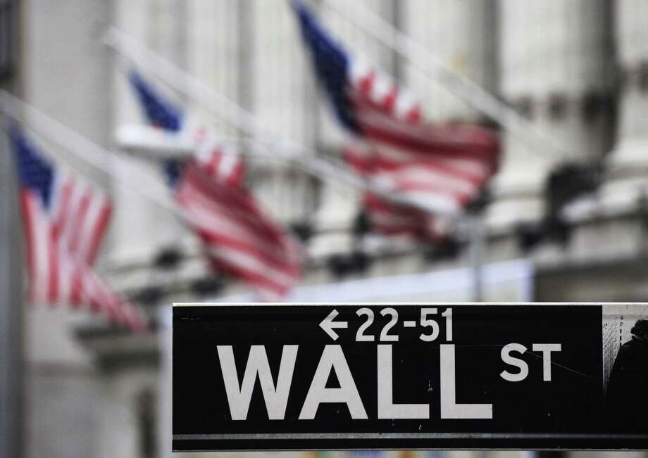 FILE - This April 22, 2010, file photo, shows a Wall Street sign in front of the New York Stock Exchange.  Asian shares pushed higher Friday, June 19, 2015,  following a rally in U.S. markets, but China's benchmark sank again on worries over the potential impact of a flurry of initial public offerings and moves by regulators to curb margin trading. Photo: The Associated Press / AP