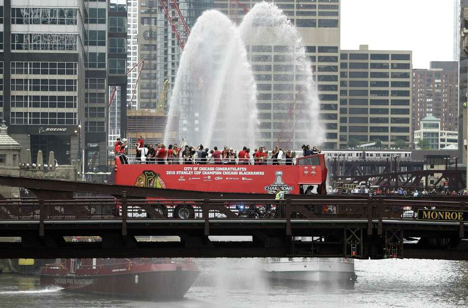 Chicago Blackhawks players, with the Stanley Cup, ride in an open-top bus across the Monroe Street Bridge over the Chicago River during a parade celebrating their Stanley Cup championship on Thursday. Photo: Charles Rex Arbogast — The Associated Press   / AP