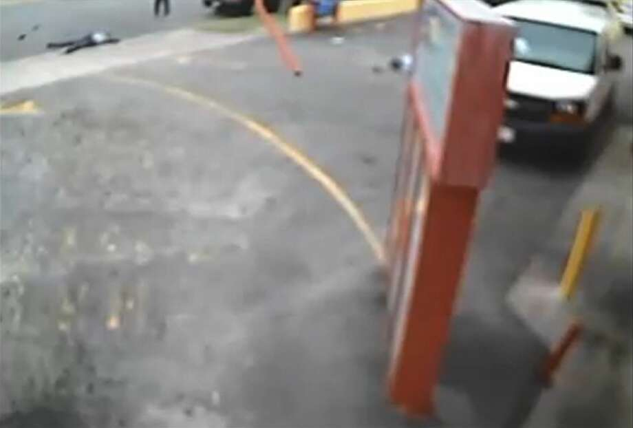 "In this still image from a security video made on Jan. 29, 2015, and provided by the Los Angeles Superior Court where it was entered into evidence, two men lie on the ground after an SUV driven by rap music mogul Marion ""Suge"" Knight ran over them at a fast food restaurant in Compton, Calif., near Los Angeles. Cle ""Bone"" Sloan, top left, survived, but Terry Carter, partially obscured behind the sign, later died. A judge ruled on Thursday, April 16, 2015, that Knight will stand trial on murder and attempted-murder charges. (Los Angeles Superior Court via AP) Photo: AP / Los Angeles Superior Court"