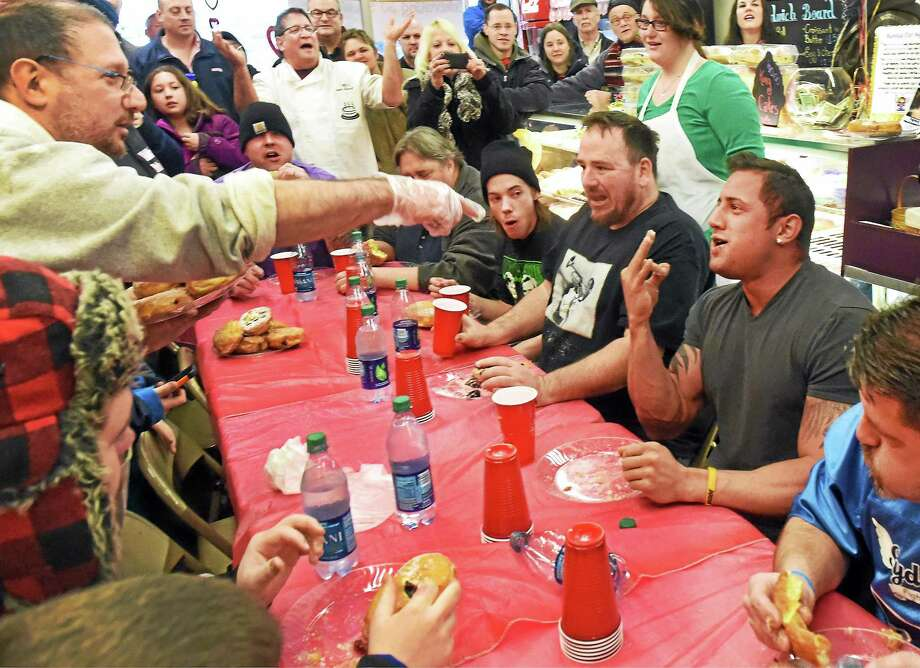 "(Peter Hvizdak - New Haven Register)  Manny ""Manimal"" Cambra of Bethel, Conn., second from right,  who ate a dozen donuts in Eddy's Bake Shop 17th annual paczki eating contest  in Ansonia, Conn., is declared the 2015 champion as the bakery celebrates Fat Tuesday, February 17, 2015. Contestants have five minutes to eat as many of the deep fried polish-style donuts as they can.  Eddy's Bake Shop is celebrating its 50th Anniversary. The traditions of eating paczkis or pancakes on Fat Tuesday are a final celebration on the eve of Lent, a season of penance marking Jesus' 40 days in the wilderness. The six weeks of Lent lead up to Holy Week and Easter, which this year falls on April 5. Photo: ©2015 Peter Hvizdak / ©2015 Peter Hvizdak"