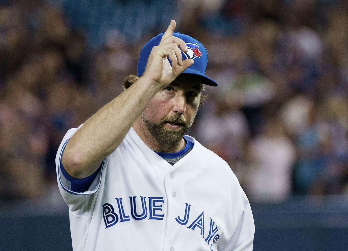 Toronto Blue Jays starting pitcher R.A. Dickey salutes the crowd as he leaves Thursday's game against the New York Mets during eighth inning.