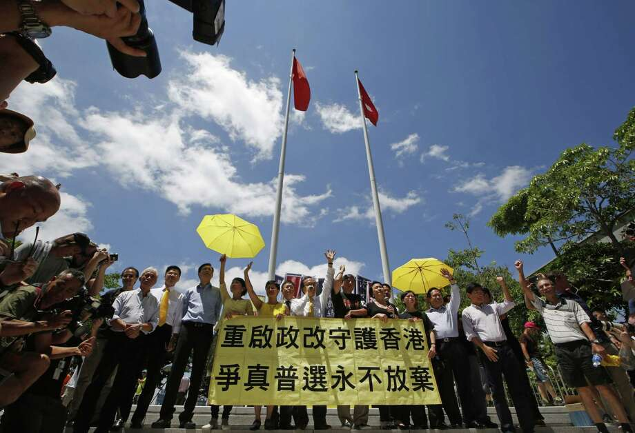 Pro-democracy lawmakers celebrate outside the Legislative Council in Hong Kong, Thursday, June 18, 2015. The Hong Kong government's controversial Beijing-backed election reforms were defeated Thursday by pro-democracy lawmakers. (AP Photo/Kin Cheung) Photo: AP / AP