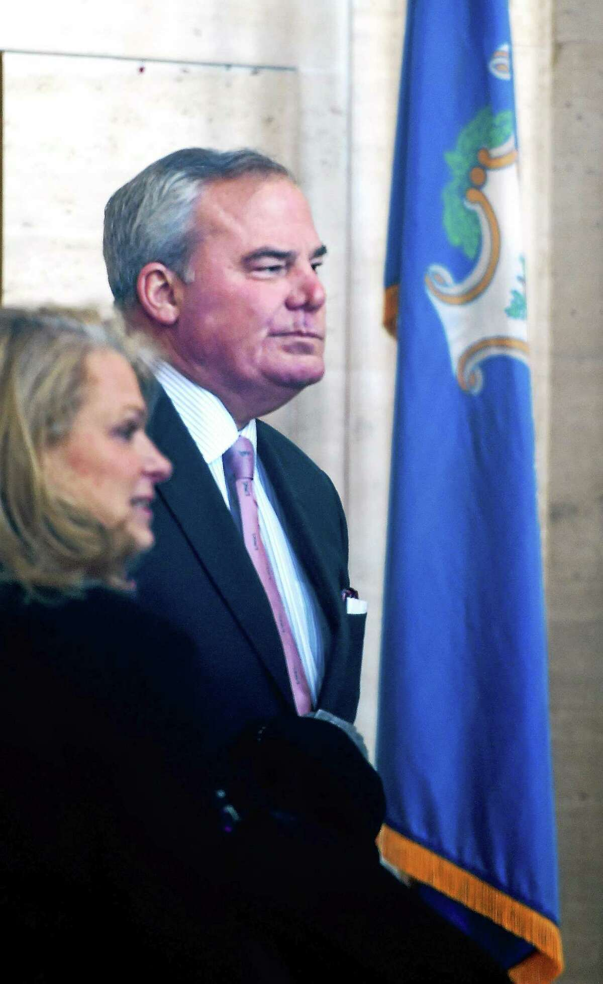 Former Connecticut Governor John Rowland, center, waits inside the lobby of Federal Court in New Haven before sentencing with his wife, Patty, left, Wednesday.