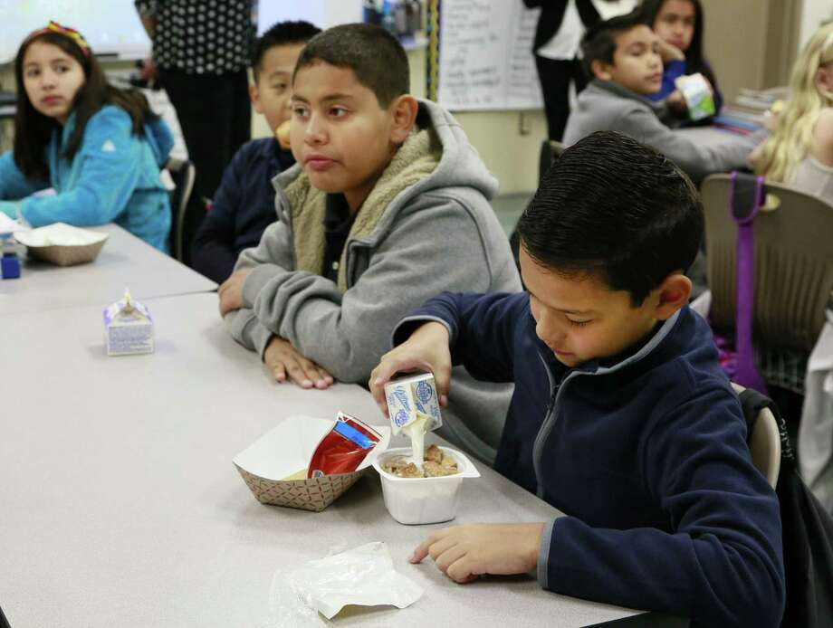 In this Wednesday, April 8, 2015 photo, students are served breakfast at the Stanley Mosk Elementary School in Los Angeles. In this Los Angeles Unified School District program, and in other major urban school districts, breakfast is increasingly being served inside the classroom. The number of breakfasts served in the nation's schools has doubled in the last two decades, a surge driven largely by a change in how districts deliver the food. Instead of providing low-income students free or reduced-price meals in the cafeteria, they're increasingly serving all children in the classroom. Photo: AP Photo/Nick Ut    / AP