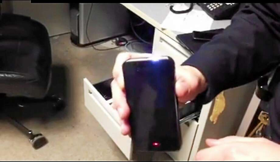 A screenshot from a video posted on Facebook by the West Haven Police shows an iPhone disguised as a stun gun that police said they found in the possession of a man they were arresting. Photo: Contributed Photo — West Haven Police