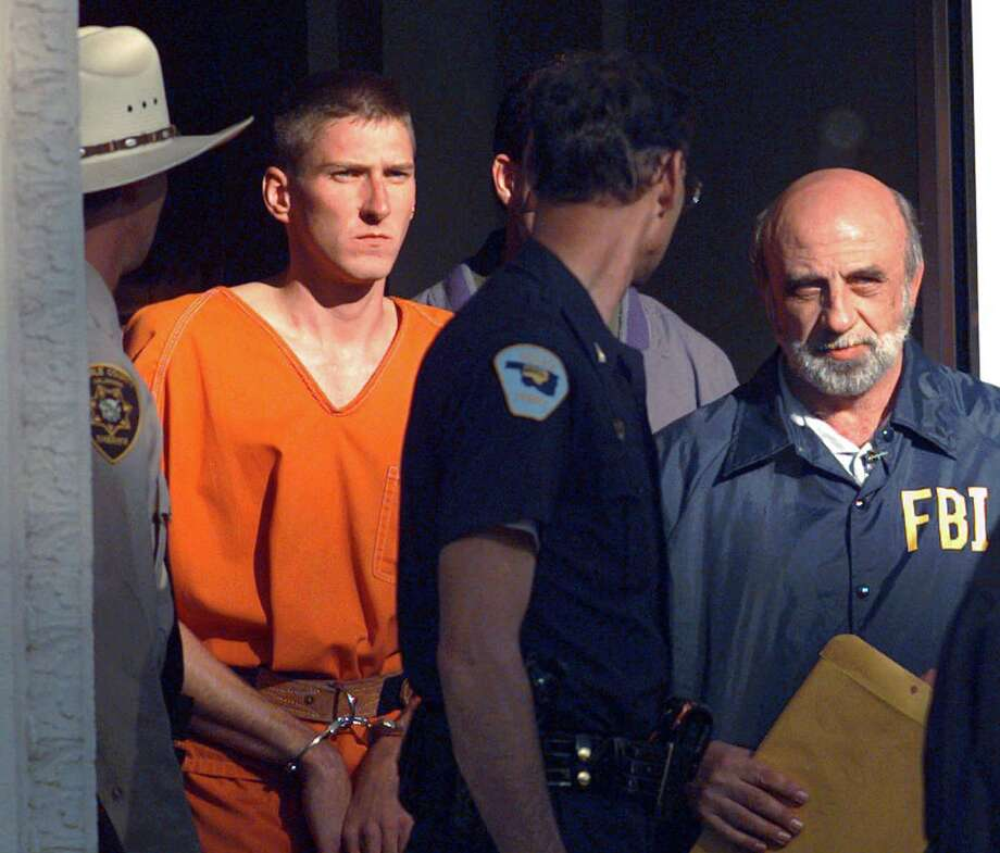 FILE - In this April 21, 1995 file photo, Timothy James McVeigh is lead out of the Noble County Courthouse by state and federal law enforcement officials in Perry, Okla., after being identified as a suspect in the bombing of the Oklahoma City Federal building. McVeigh was sentenced to death and executed. Photo: (AP Photo/John Gaps III) / AP