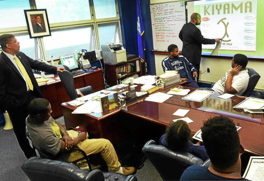 Attorney Michael Jefferson, a human rights activist and founder of The Kiyama Movement, right, explains the Kiyama  self-improvement program for young men, particularly young men of color, as he speaks to approximately 20 Hillhouse High School male students at the school Tuesday, May 19, 2015. Hillhouse High School principal Kermit Carolina is at far left. Photo: Peter Hvizdak - New Haven Register   / ©2015 Peter Hvizdak