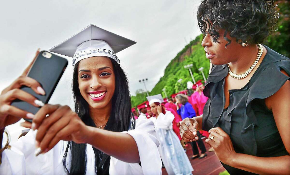 Shakira Davis takes a selfie after her assistant basketball coach Deborah Daniels-McClease helped out with her mortarboard shortly before commencement at Wilbur Cross High School in New Haven Thrusday.