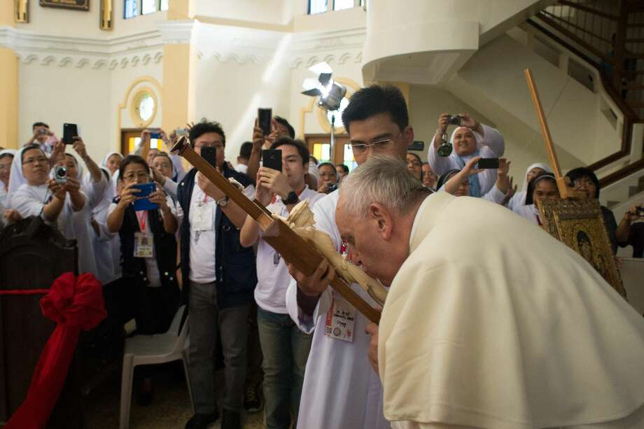 Pope Francis kisses a wooden crucifix as he he visits the Cathedral of Palo in Tacloban, Philippines, Saturday, Jan. 17, 2015. Francis traveled to the far eastern Philippines to comfort survivors of devastating Typhoon Haiyan in 2013 on Saturday, but cut his own trip short because of another approaching storm (AP Photo/L'Osservatore Romano, Pool) Photo: AP / L'Osservatore Romano