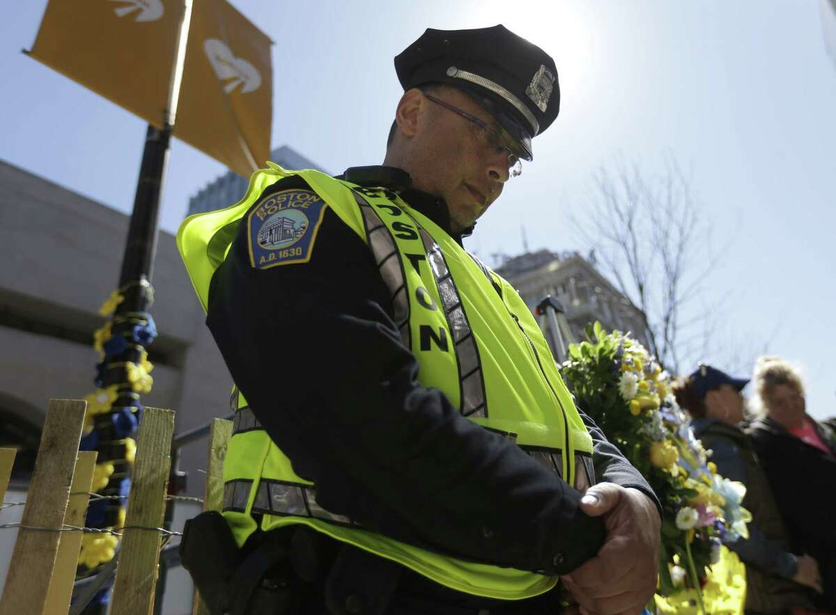 Boston Police officer Roy Boussard stands near a wreath and bows his head following a moment of silence at one of two blast sites near the finish line of the Boston Marathon, in Boston, Wednesday, April 15, 2015. Boston marked the second anniversary of the 2013 marathon bombings with a subdued remembrance that included a moment of silence, the pealing of church bells and a call for kindness. (AP Photo/Steven Senne)