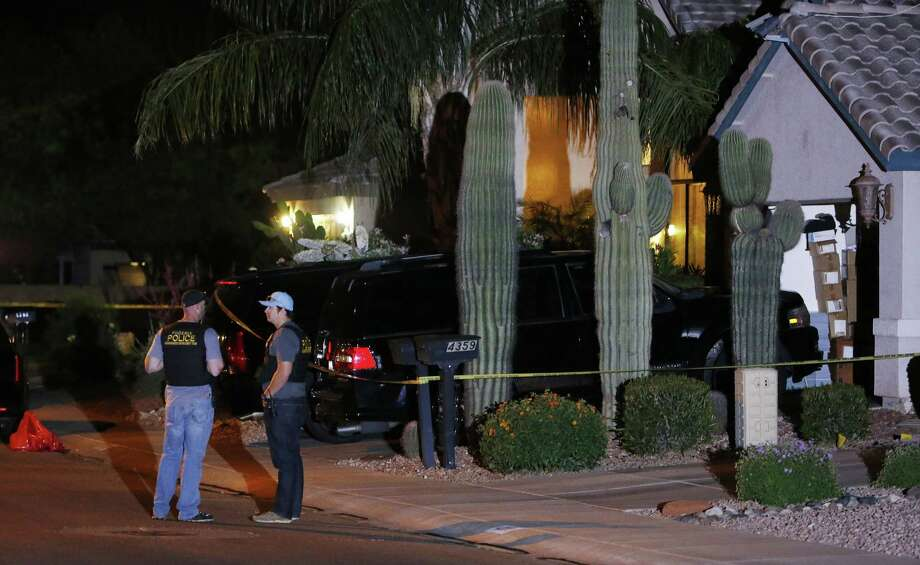 Phoenix Police Department officers stand out in front of a home where authorities say five people were killed inside after a shooting Thursday, April 16, 2015, in Phoenix. The names and ages of the three men and two women weren't immediately released, but police said they all were adults. (AP Photo/Ross D. Franklin) Photo: AP / AP