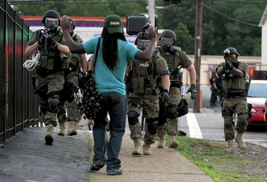 In this Aug. 11, 2014 photo, police wearing riot gear walk toward a man with his hands raised in Ferguson, Mo. Photo: AP Photo/Jeff Roberson, File   / AP