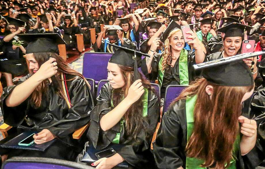(John Vanacore/for the New Haven Register)  Grads adjust their tassles at the University of New Haven 2015 Commencement Ceremony at Toyota Oakdale Theatre in Wallingford Sunday. Photo: Journal Register Co. / John Vanacore/REGISTER