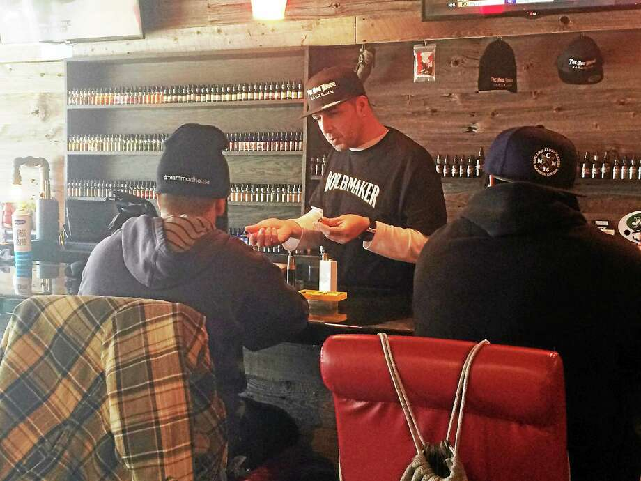 Jay Cancel, the manager of The Mod House Vaporium in Milford, shows two customers how to use vaping products at the shop's bar Friday afternoon. State lawmakers are considering proposals to increase restrictions products that create vapor instead of smoke, such as electronic cigarettes. Photo: (Wes Duplantier — New Haven Register)