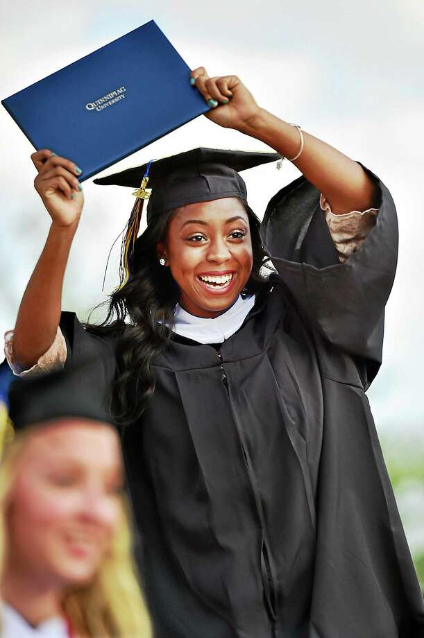 Catherine Avalone/New Haven Register  Diamond Lashai Hawkins raises her diploma after receiving a bachelor of arts degree at commencement exercises at Quinnipiac University Sunday. Photo: Journal Register Co. / New Haven RegisterThe Middletown Press