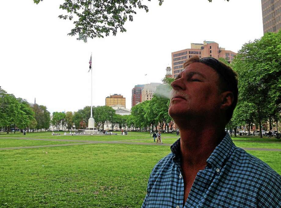 "Jerry Hackett smokes a cigarette, on the New Haven Green Monday. He supports tobacco bans at places like hospital areas and school grounds but called bans at locations like public parks ""absurd."" Photo: Evan Lips — New Haven Register"